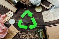 Απορρίματα για την ανακύκλωση με την ανακύκλωση του συμβόλου στην ξύλινη τοπ άποψη υποβάθρου Στοκ Εικόνες