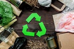Απορρίματα για την ανακύκλωση με την ανακύκλωση του συμβόλου στην ξύλινη τοπ άποψη υποβάθρου Στοκ φωτογραφία με δικαίωμα ελεύθερης χρήσης