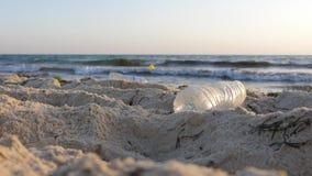 Απορρίματα και πλαστικά μπουκάλια στην παραλία κοντά στη θάλασσα Έννοια ρύπανσης φιλμ μικρού μήκους