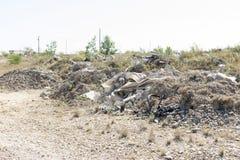 Απορρίμματα και παλαιά οικοδομικά υλικά που μολύνουν ένα κενό μέρος Στοκ Φωτογραφίες