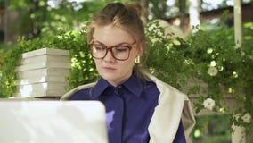 Απορροφημένη νέα γυναίκα στα γυαλιά που λειτουργούν με το lap-top σε έναν θερινό καφέ απόθεμα βίντεο