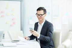 Αποστολή κειμενικών μηνυμάτων επιχειρηματιών στον εργασιακό χώρο Στοκ Εικόνες