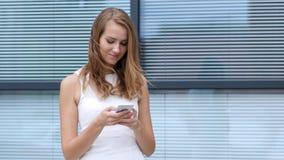 Αποστολή κειμενικών μηνυμάτων σε Smartphone από το όμορφο κορίτσι, έξω από το γραφείο Στοκ φωτογραφία με δικαίωμα ελεύθερης χρήσης
