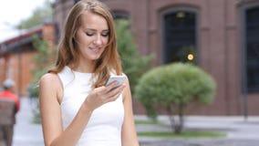 Αποστολή κειμενικών μηνυμάτων σε Smartphone από το όμορφο κορίτσι, έξω από το γραφείο Στοκ Εικόνες
