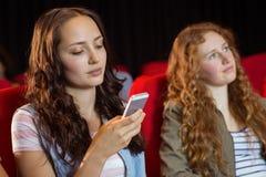 Αποστολή κειμενικών μηνυμάτων γυναικών σε την κινητή κατά τη διάρκεια του κινηματογράφου Στοκ Φωτογραφία