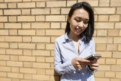 Αποστολή κειμενικών μηνυμάτων επιχειρηματιών χαμόγελου νέα ασιατική στο τηλέφωνο κυττάρων ενάντια στο τουβλότοιχο Στοκ Φωτογραφίες
