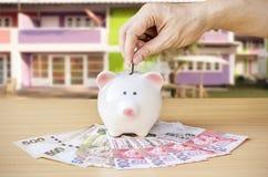 Αποταμίευση, αρσενικό χέρι που βάζει ένα νόμισμα στη piggy τράπεζα και τα χρήματα στοκ φωτογραφίες με δικαίωμα ελεύθερης χρήσης