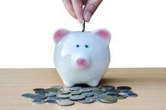 Αποταμίευση, αρσενικό χέρι που βάζει ένα νόμισμα στη piggy τράπεζα και τα χρήματα στοκ εικόνα με δικαίωμα ελεύθερης χρήσης
