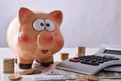 Αποταμίευση και λογιστική με τα piggy χρήματα και τον υπολογιστή τραπεζών fron Στοκ Εικόνες