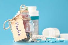Αποταμίευση χρημάτων για ιατρικό στο μπουκάλι γυαλιού Στοκ φωτογραφία με δικαίωμα ελεύθερης χρήσης