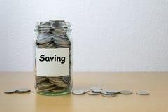 Αποταμίευση χρημάτων για την αποταμίευση στο μπουκάλι γυαλιού Στοκ Εικόνες