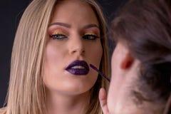 Αποτελέστε στη διαδικασία, ο καλλιτέχνης Makeup εφαρμόζει το κραγιόν, χρωματίζοντας το χείλι στοκ εικόνα
