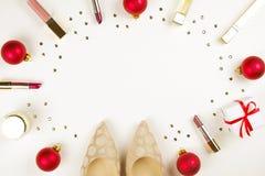 Αποτελέστε τα προϊόντα με τη διακόσμηση Χριστουγέννων και τα παπούτσια της χρυσής γυναίκας στο άσπρο υπόβαθρο με το διαστημικό επ στοκ εικόνες