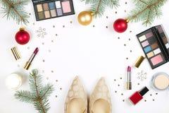 Αποτελέστε τα προϊόντα με τη διακόσμηση Χριστουγέννων και τα παπούτσια της χρυσής γυναίκας στο άσπρο υπόβαθρο με το διαστημικό επ στοκ φωτογραφία