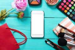 Αποτελέστε την έννοια Καλλυντικό on-line Πλαίσιο των καλλυντικών, κενή κινητή οθόνη στο μπλε ξύλινο υπόβαθρο Τοπ όψη διάστημα αντ Στοκ Εικόνες