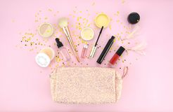 Αποτελέστε την τσάντα και το σύνολο επαγγελματικών διακοσμητικών καλλυντικών, makeup εργαλεία και εξάρτημα στο ρόδινο υπόβαθρο Ομ Στοκ Εικόνες