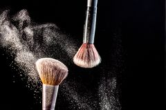 Αποτελέστε τις καλλυντικές βούρτσες με τη σκόνη να κοκκινίσουν έκρηξη στο μαύρο υπόβαθρο Φροντίδα δέρματος ή έννοια μόδας στοκ φωτογραφίες