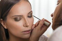 Αποτελέστε τον καλλιτέχνη ισχύοντα eyeliner στα βλέφαρα στοκ εικόνες με δικαίωμα ελεύθερης χρήσης