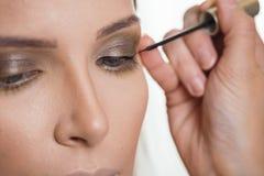 Αποτελέστε τον καλλιτέχνη ισχύοντα eyeliner στα βλέφαρα του θηλυκού πελάτη στοκ φωτογραφίες με δικαίωμα ελεύθερης χρήσης