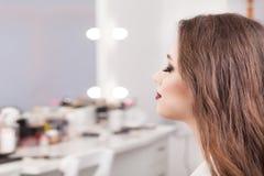 Αποτελέστε τον καλλιτέχνη που εφαρμόζει τη σκιά ματιών σε μια γυναίκα στοκ φωτογραφία με δικαίωμα ελεύθερης χρήσης