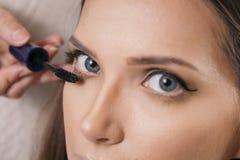 Αποτελέστε τον καλλιτέχνη που εφαρμόζει mascara του θηλυκού πελάτη eyelashes στοκ φωτογραφίες