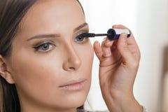Αποτελέστε τον καλλιτέχνη που εφαρμόζει mascara του πελάτη eyelashes στοκ εικόνες