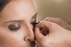 Αποτελέστε τον καλλιτέχνη που τοποθετεί τα τεχνητά eyelashes στοκ φωτογραφία με δικαίωμα ελεύθερης χρήσης