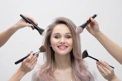 Αποτελέστε το σαλόνι, makeup εργασία καλλιτεχνών Τέσσερα χέρια με τους θυσάνους και το πρόσωπο ενός χαμογελώντας όμορφου κοριτσιο στοκ εικόνα με δικαίωμα ελεύθερης χρήσης
