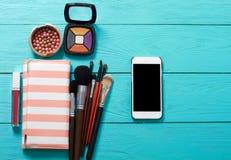 Αποτελέστε τα εξαρτήματα Τοπ όψη μπλε ξύλινος ανασκόπησης Κινητό τηλέφωνο με την κενή οθόνη καλλυντικά προϊόντα Στοκ Εικόνες