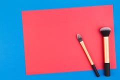Αποτελέστε τις βούρτσες με το κόκκινο κενό έγγραφο για το μπλε υπόβαθρο στοκ εικόνες με δικαίωμα ελεύθερης χρήσης