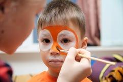 Αποτελέστε τον καλλιτέχνη που κάνει τη μάσκα τιγρών για το παιδί στοκ φωτογραφία