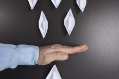 Αποτρέψτε την επιχειρησιακή έννοια Επιχείρηση στάσεων το χέρι επιχειρηματιών ` s σταματά τα σκάφη εγγράφου του origami κρίση στην Στοκ Εικόνες