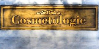 Αποτυπωμένο σε ανάγλυφο χρυσός Cosmetology επιγραφής στον άσπρο τοίχο στοκ εικόνα