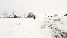 Αποφορτιμένος λόφος χιονιού αγοριών απόθεμα βίντεο