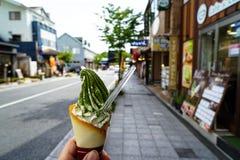 Απολαμβάνοντας το παγωτό γάλακτος μαλακό εξυπηρετήστε τον κώνο με την πράσινη νιφάδα τσαγιού pow στοκ εικόνα με δικαίωμα ελεύθερης χρήσης
