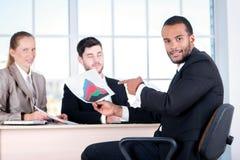 Απολογισμοί ελέγχου Τρεις επιτυχείς επιχειρηματίες που κάθονται στο τ Στοκ Φωτογραφίες