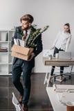 Απολυθείς επιχειρηματίας με το κουτί από χαρτόνι στην αρχή, 0 προϊστάμενος πίσω Στοκ Φωτογραφίες