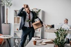 Απολυθείς επιχειρηματίας με το κουτί από χαρτόνι στην αρχή, προϊστάμενος πίσω Στοκ φωτογραφία με δικαίωμα ελεύθερης χρήσης
