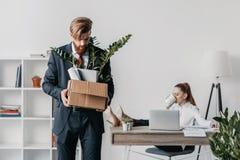 Απολυθείς επιχειρηματίας με το κουτί από χαρτόνι στην αρχή, προϊστάμενος πίσω Στοκ Εικόνες