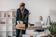 Απολυθείς επιχειρηματίας με το κουτί από χαρτόνι στην αρχή, προϊστάμενος πίσω Στοκ εικόνες με δικαίωμα ελεύθερης χρήσης
