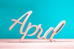 Απρίλιος - δεύτερος μήνας της άνοιξη Ξύλινη χαρασμένη λέξη στο σκούρο μπλε υπόβαθρο Κάρτα για την ημέρα ανόητων, την 1η Απριλίου, στοκ εικόνες