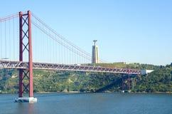 25 Απριλίου γέφυρα και Χριστός το άγαλμα βασιλιάδων Στοκ Εικόνες