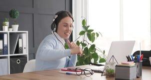 Απρόσεκτος ανώτερος υπάλληλος που έχει τη διασκέδαση ακούοντας και τραγουδώντας τη μουσική στο γραφείο γραφείων απόθεμα βίντεο