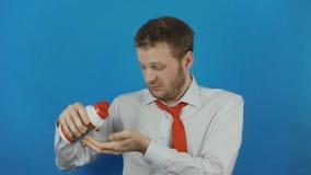 Απρόσεκτος επιχειρηματίας με το διαιτητικό συμπλήρωμα ως κάψες ή ταμπλέτες ή χάπια απόθεμα βίντεο