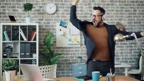 Απρόσεκτος χορός εργαζομένων γραφείων που ακούει τη μουσική που ρίχνει τα έγγραφα και το σημειωματάριο απόθεμα βίντεο