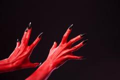 Απόκοσμα κόκκινα χέρια διαβόλων με τα μαύρα καρφιά, πραγματική σώμα-τέχνη Στοκ φωτογραφία με δικαίωμα ελεύθερης χρήσης