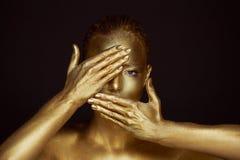 Απόκοσμα χρυσά κορίτσια πορτρέτου, χέρια κοντά στο πρόσωπο Πολύ λεπτός και θηλυκός Τα μάτια είναι ανοικτά η κλίση πλαισίων δίνει  στοκ εικόνα με δικαίωμα ελεύθερης χρήσης
