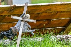 απόκοσμος ξύλινος σταυρός και γάντι στο χλοώδες έδαφος στοκ φωτογραφίες