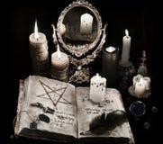 Απόκρυφη ακόμα ζωή με το μαύρο μαγικό βιβλίο, κεριά και mirrow Στοκ Εικόνες