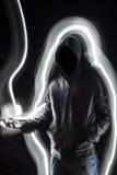 Απόκρυφο μαύρο με κουκούλα άτομο που στέκεται στο σκοτάδι Στοκ Εικόνες